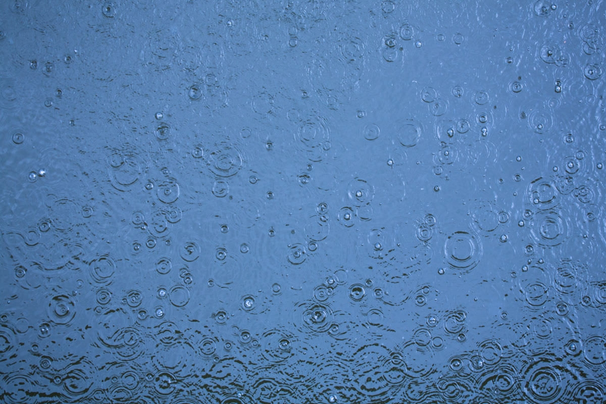 Rain Drop Ripples On The Blue Water