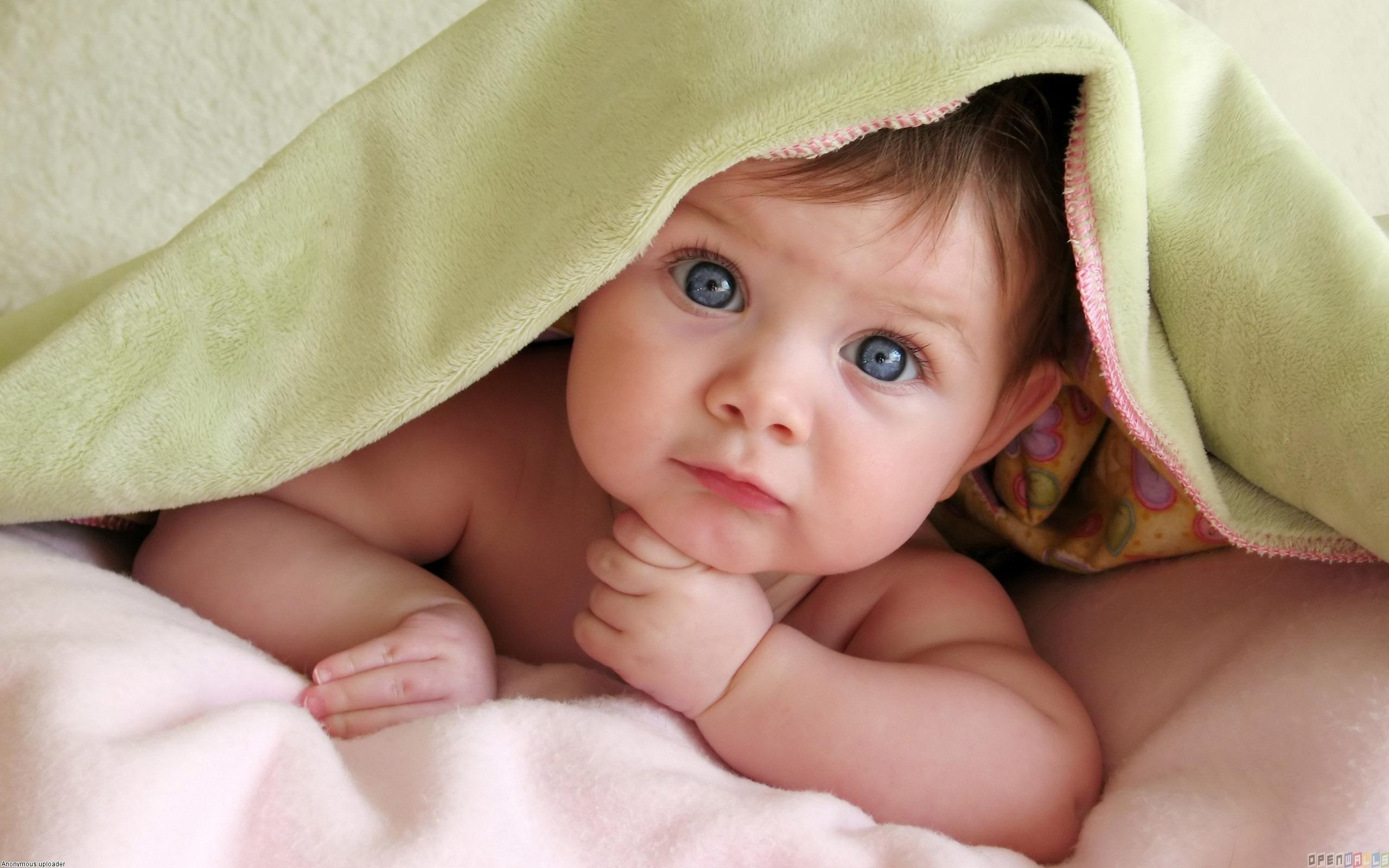 Cute Baby Girl in Bedsheet Wallpaper
